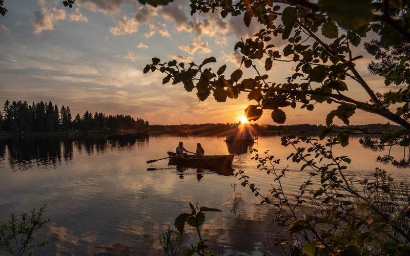 AuroraHut glass igloo boat and a rowboat floating at lake Ranua
