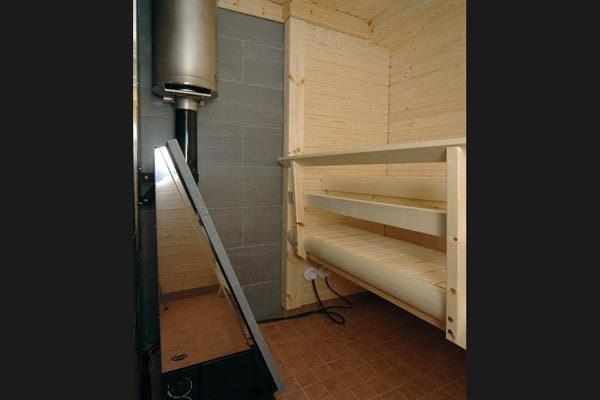 Sisäsauna - Sisällä on sauna, jonka laavukiukaan voi lämmittää puulla tai sähköllä.