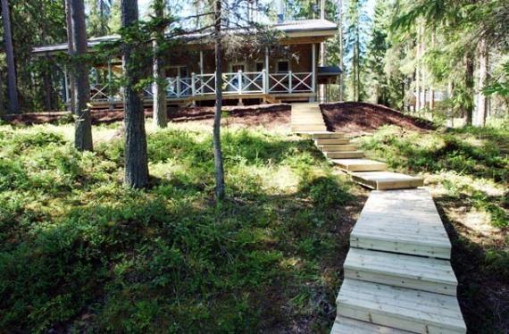 Piha-alue - Huvila rantalaiturin suunnasta. Piha-alue on pääosin luonnonmukaista metsää. Rantaan menevät portaat ja puukäytävä.