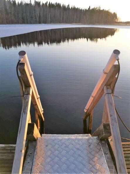 Laiturin portaissa lämmitetyt kaiteet talviuimareille - Talvella pumppu pitää auki avantoa.