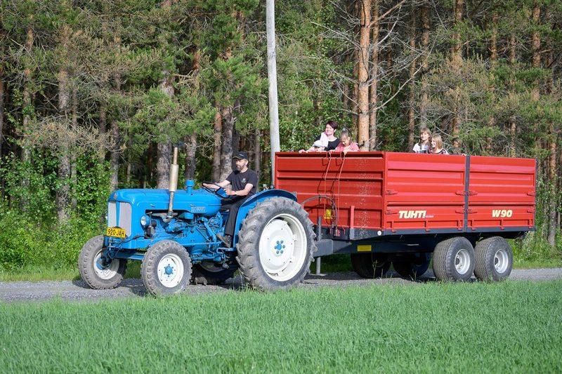 Traktorikyyti heinäpaalien päällä istuskellen