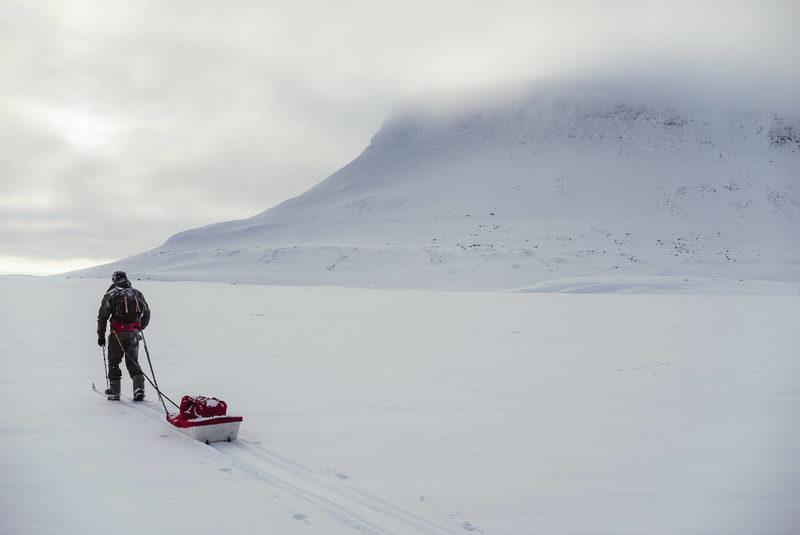Hiihtovaellus ahkion kanssa - Hiihtäjä vetää ahkiota lumisessa maisemassa, takana näkyy tunturi