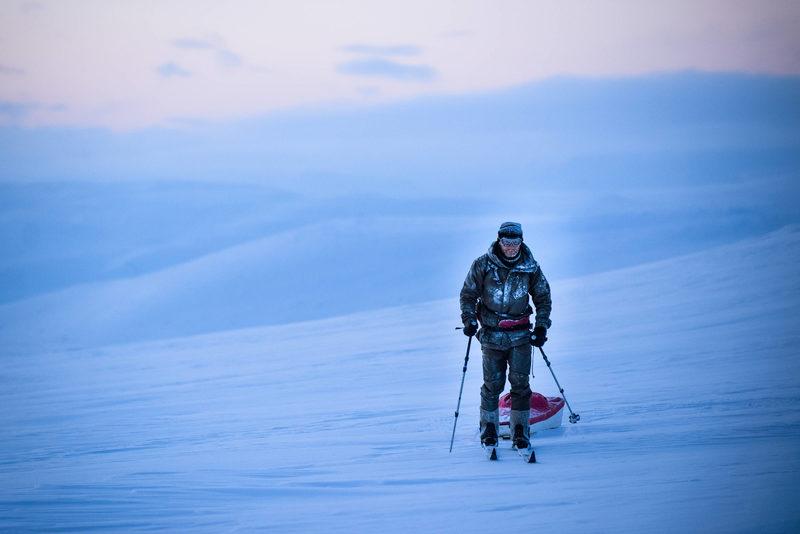 Hiihtäjä ja ahkio - Mies hiihtää ahkion kanssa lumisessa maisemassa