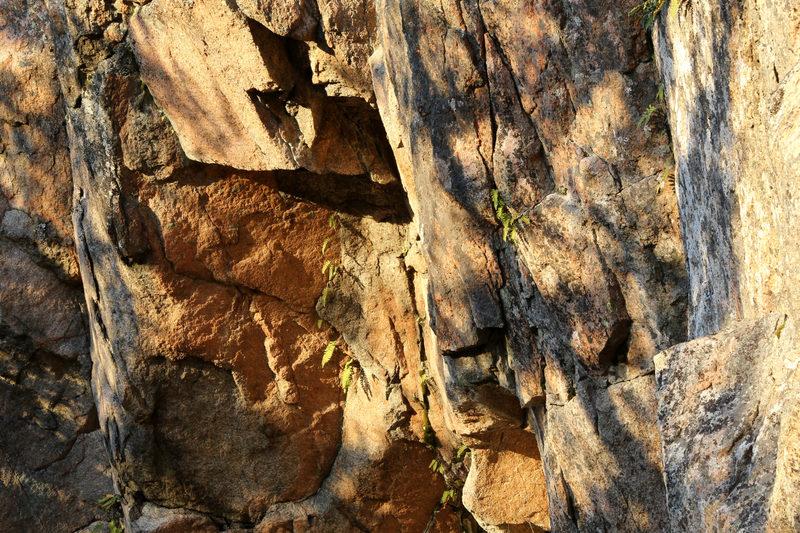 Taikapolku Pyhävuoren seinillä ja kivillä - Ilta-aurinko värittää Pyhävuoren jyrkänteet lämpimän punaisilla sävyillä. Retkikahvit sopivat hyvin tunnelmaan.