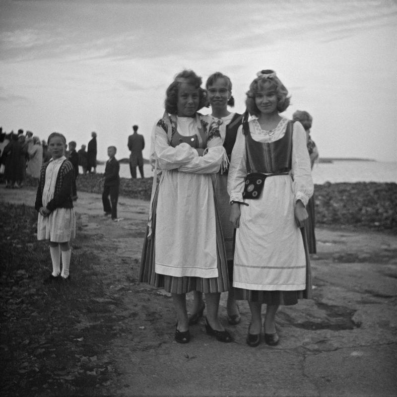 1950 -luvun loppu, nuoria naisia Juhannuksen vietossa Vallisaaressa. - Vasemmalla taustalla paikalle kerääntynyt väki seuraa kokon polttamista. Taivaanrannassa häämöttää Isosaari.