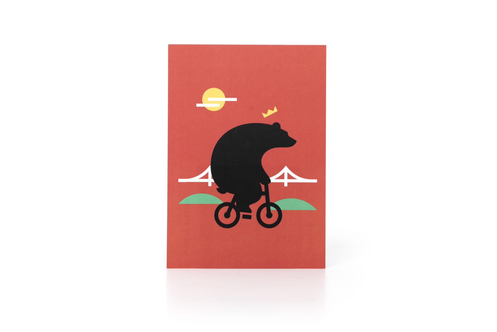 Postikortti pyöräilevä karhu